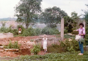 """Visiting all that remained of the duplex housing for single missionary ladies at the old site (about 1985). Flooring, siding, roofing, windows, and doors had all been transported to the relocation site for use in buildings there. Note the rising waters of the reservoir in the background. To our left is the boatman. In the center with back to camera is Linette McDaniel. On the right, pointing to the """"ruins"""", is Jan Stretton, missionary nurse, who used to live in this building."""