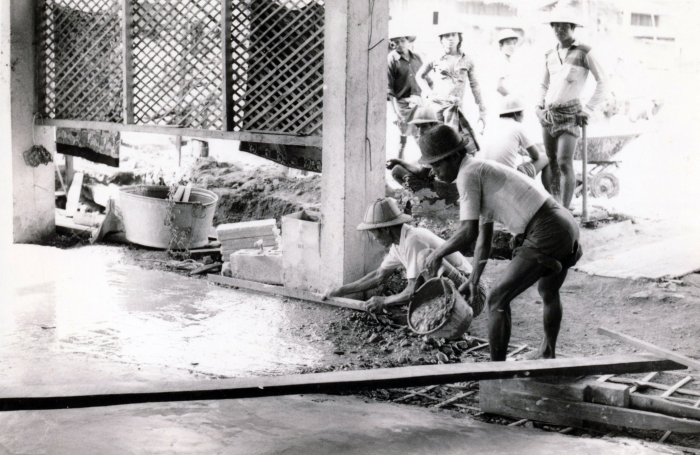 """Pouring cement floor for what was to become the large open inpatient ward. Note the bamboo """"reinforcing bars"""" underneath."""