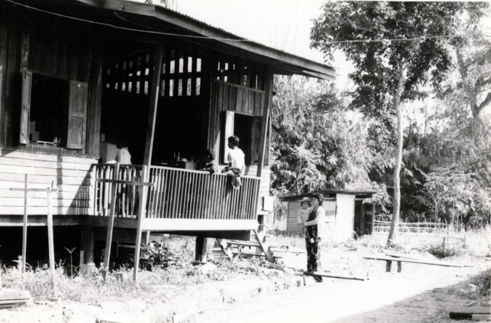 Wooden guest house used as temporary pharmacy, lab, outpatient examining room, inpatient ward, and operating room while the new hospital building (behind us) was being built at the Huay Malai site. Note the outhouse in the background.