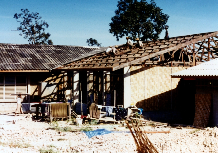 New hospital in Huey Malai under construction about 1984. Note use of woven bamboo for the wall on the near end of the building and the use of old roofing salvaged from the original hospital building.